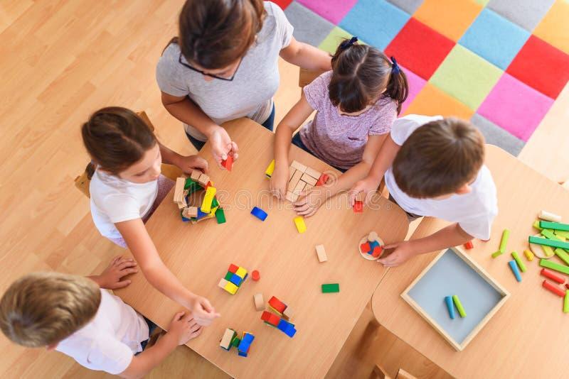 Förskole- lärare med barn som spelar med färgrika trädidaktiska leksaker på dagiset arkivfoton