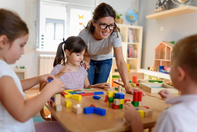 Förskole- lärare med barn som spelar med färgrika trädidaktiska leksaker på dagiset royaltyfri bild