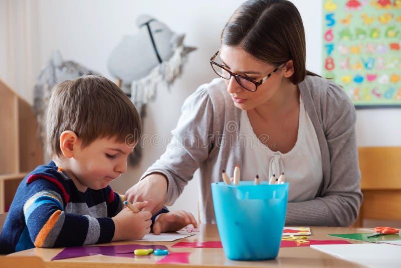 Förskole- lärare med barnet på dagiset - idérika Art Class arkivfoton
