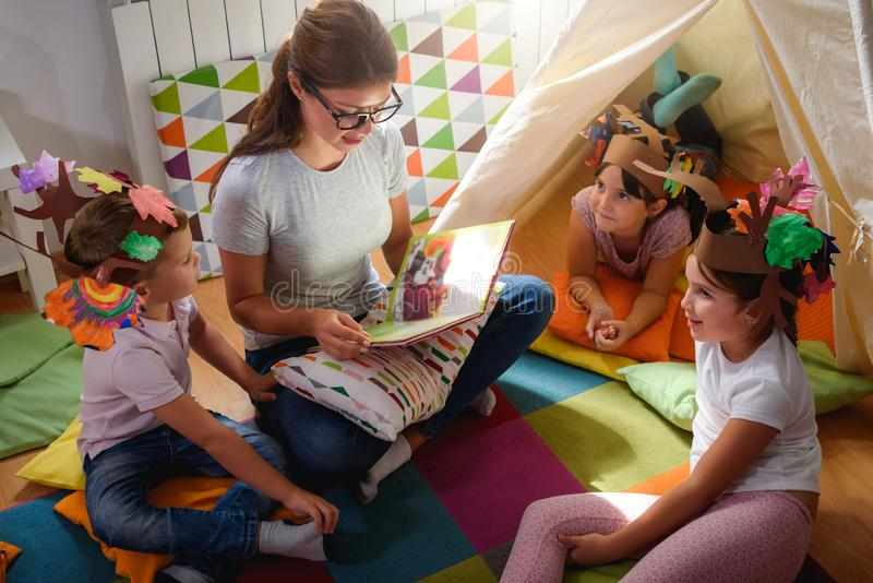 Förskole- lärare som läser en berättelse till barn på dagiset arkivfoto