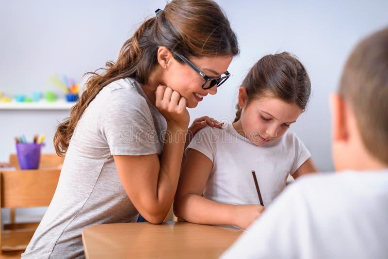 Förskole- lärare som ser det smarta barnet som lär att skriva och dra royaltyfri bild