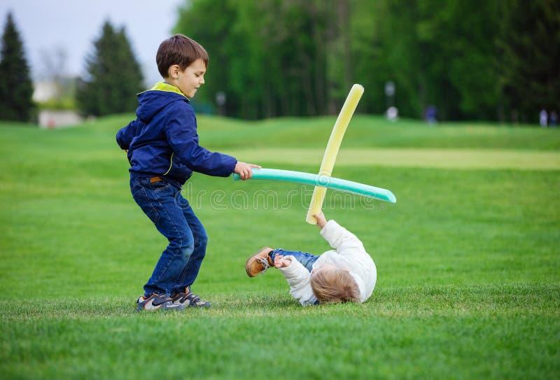 Förskole- pojkar som slåss med leksaksvärd arkivbild
