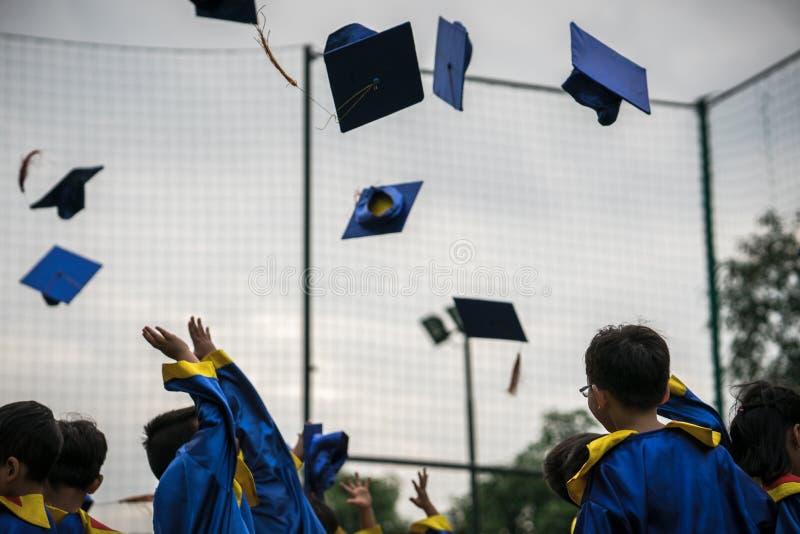 Förskole- ungar som bär den avlade examen klänningen som kastar locket och diplomaten i himmel i graderad berömdag royaltyfria bilder