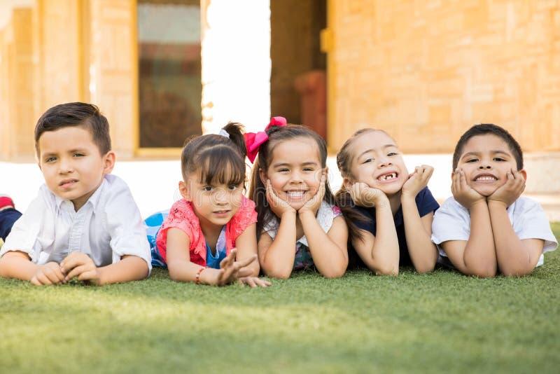 Förskole- vänner som ligger på gräset royaltyfri fotografi