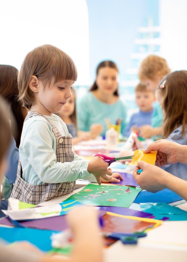 Förskolebarn grupperar med läraren i artclass royaltyfria foton