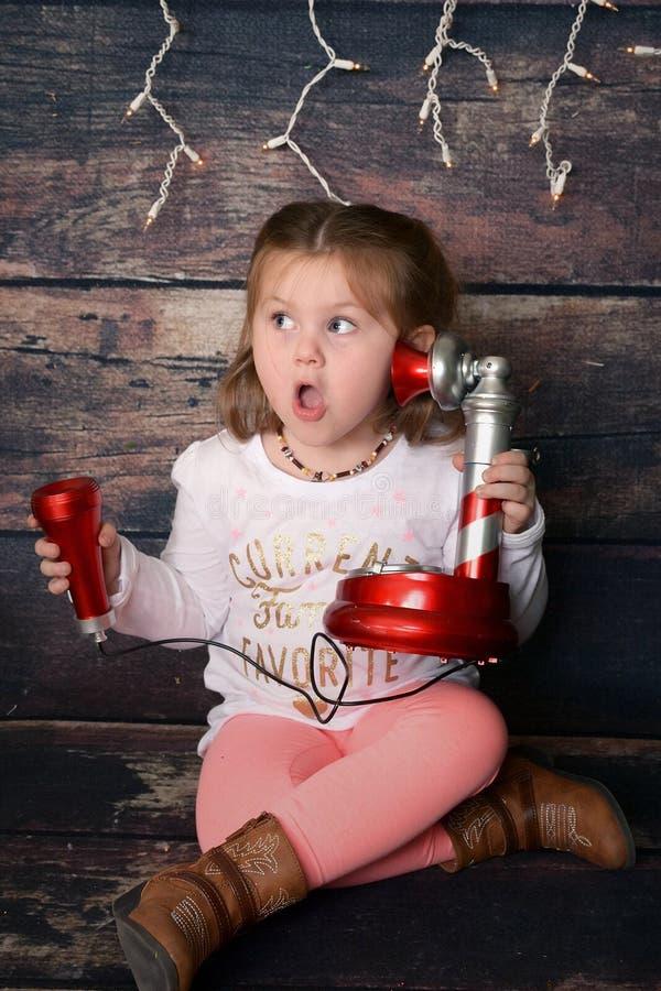 Förskolebarn på telefonen med jultomten royaltyfri foto