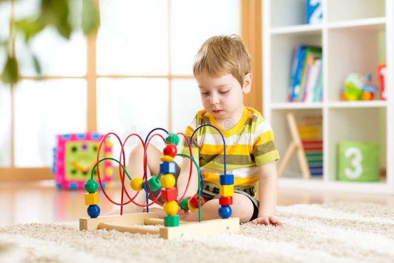 Förskolebarnbarn som spelar med den färgrika leksaken Lura att spela med den bildande träleksaken på dagis- eller daycaremitten L royaltyfri fotografi