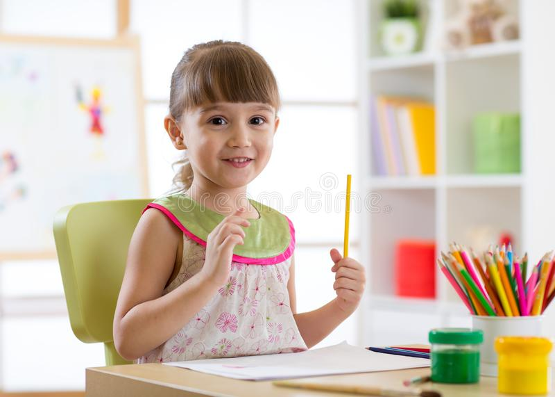 Förskolebarnbarnteckning och färgläggning vid blyertspennor royaltyfria foton