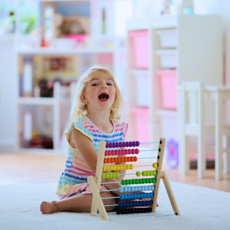 Förskolebarnflicka som spelar med kulrammet arkivfoton