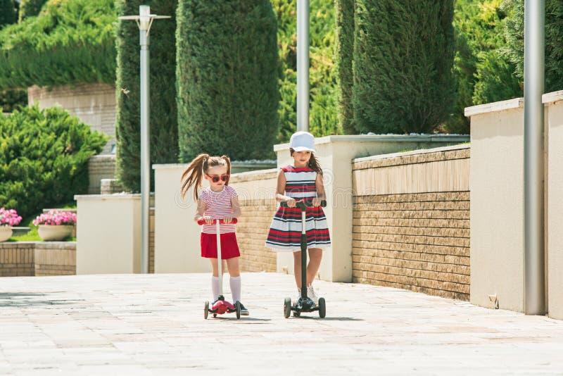 Förskolebarnflickor som utomhus rider sparkcykeln fotografering för bildbyråer