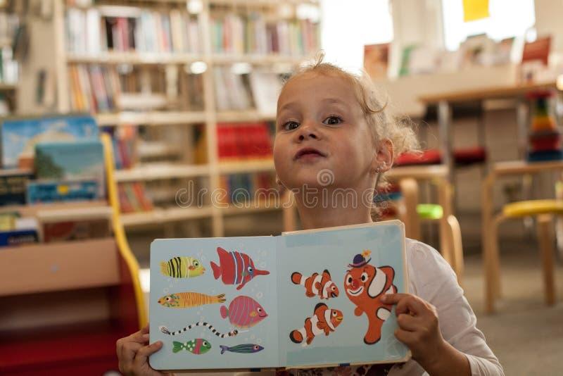 Förskolebarnliten flickasammanträde och läsning en bok i arkiv Unge med böcker nära en bokhylla Läst lycklig, gladlynt och gullig arkivfoton