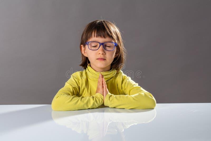 Förskolebarnyogaunge som kopplar av med mindfulness och stillhet på skolan royaltyfri fotografi