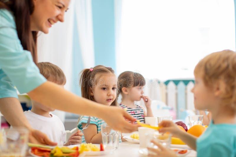 Förskoleningar som äter lunch arkivbild
