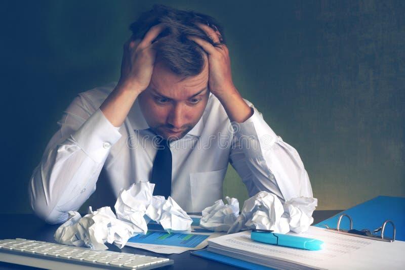 Förskräckt affärsman som ser på skrynkligt kontorspapper royaltyfri bild