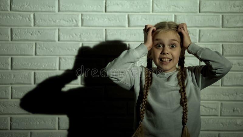 F?rskr?ckt barn som trycker p? huvudet som ser det kamera-, skr?ck- och fasabegreppet, fobi arkivbild