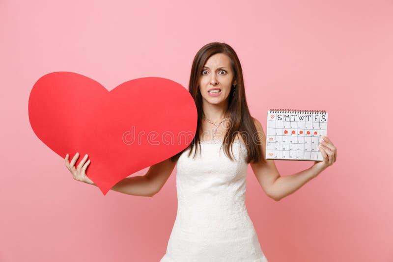 Förskräckt brudkvinna i den vita bröllopsklänningen som rymmer den kvinnliga periodkalendern för tom tom röd hjärta för att kontr royaltyfri bild