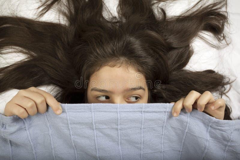 Förskräckt flickanederlag i säng royaltyfria foton