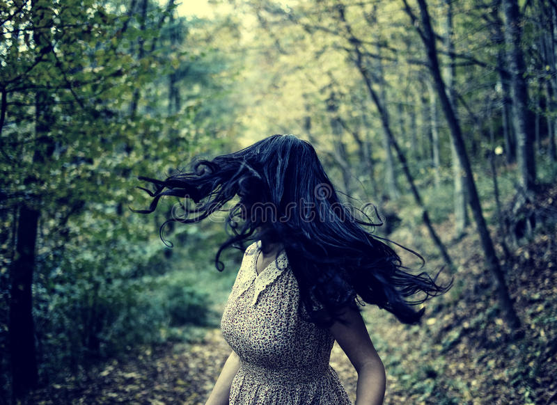 Förskräckt flickaspring i skogen