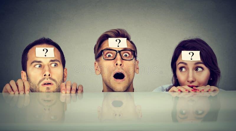 Förskräckt folk två män och en kvinna med frågefläcken som från under kikar tabellen royaltyfri fotografi