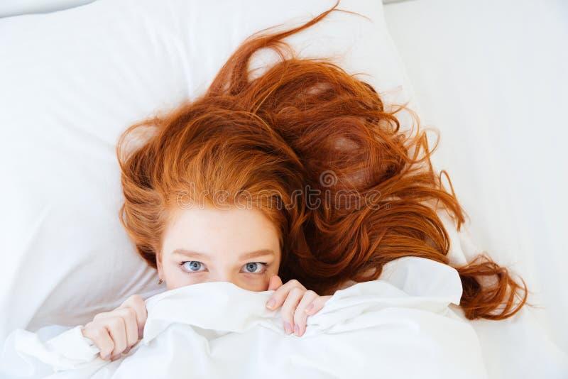 Förskräckt kvinna som ligger i säng och döljer under arket royaltyfri bild