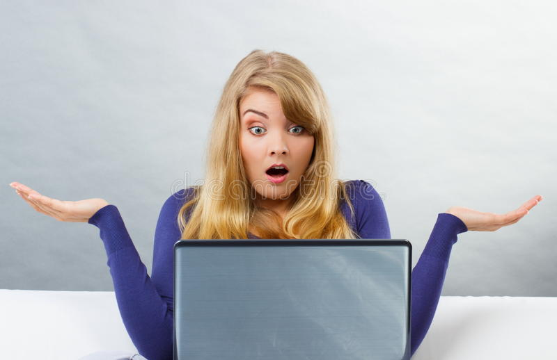 Förskräckt kvinna som rycker på axlarna skuldror och ser bärbara datorn, datorproblem royaltyfri fotografi