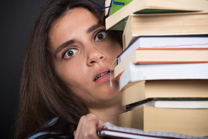 Förskräckt kvinnlig student som bär en hög av böcker royaltyfri bild