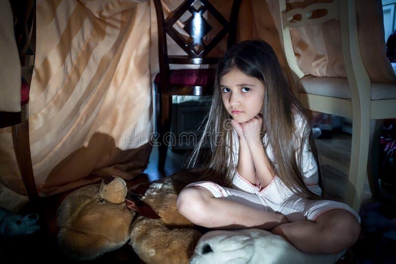 Förskräckt liten flickasammanträde på golv på den kusliga mörka natten royaltyfria bilder