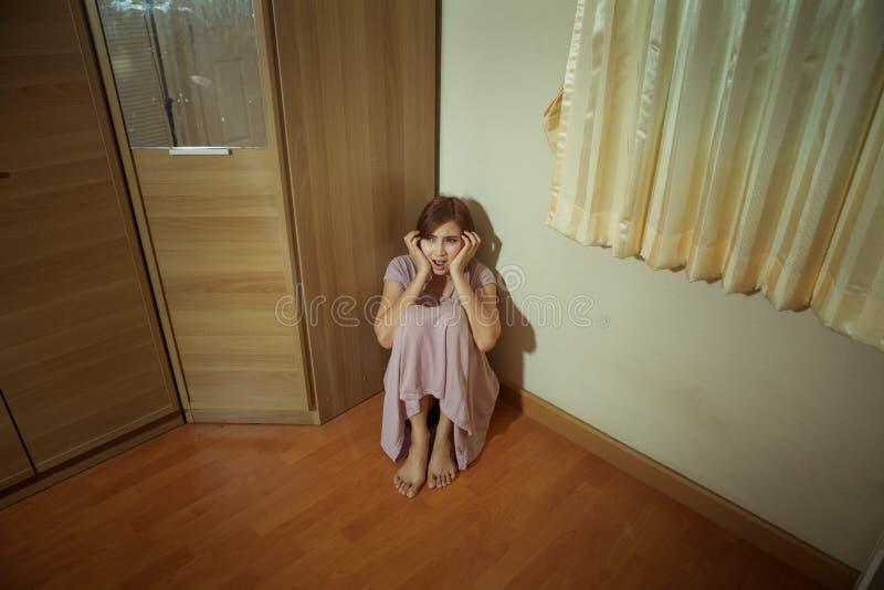 Förskräckt missbrukat kvinnasammanträde i hörnet royaltyfria bilder