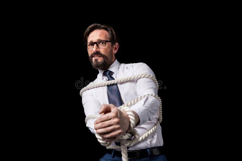 Förskräckt mitt åldras affärsman i glasögon som står bundet med repet fotografering för bildbyråer