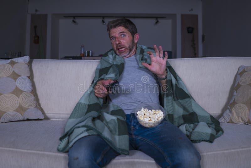 Förskräckt och rolig man bara på natten i film för fasa för vardagsrumsoffa hållande ögonen på läskig i television som skriker oc royaltyfria foton