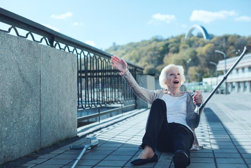 Förskräckt pensionerad dam med kryckor som faller, medan promenera arkivbild