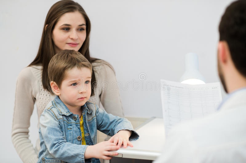 Förskräckt pojke med hans modersammanträde på den pediatriska doktorn, psykolog royaltyfria bilder