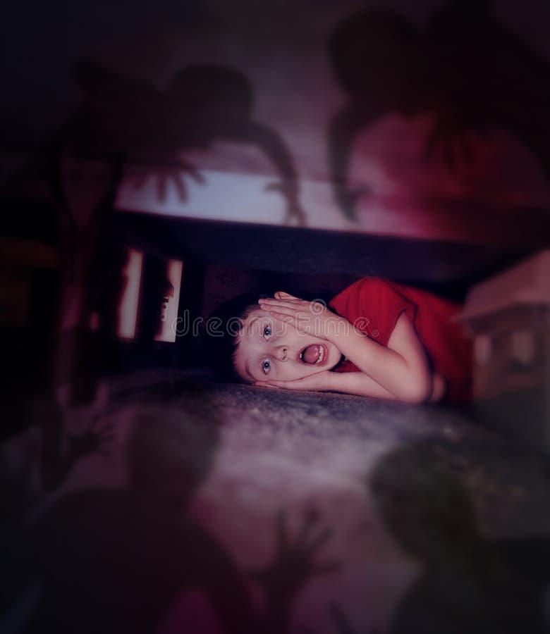 Förskräckt pojke som ser nattskuggor under säng royaltyfri bild