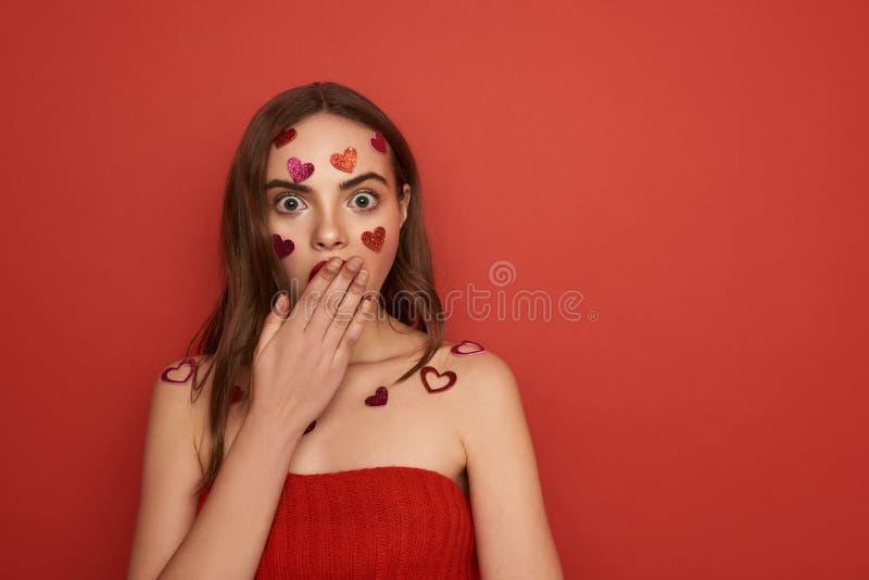 F?rskr?ckt ung dam som st?nger hennes mun med armen p? r?d bakgrund royaltyfri bild