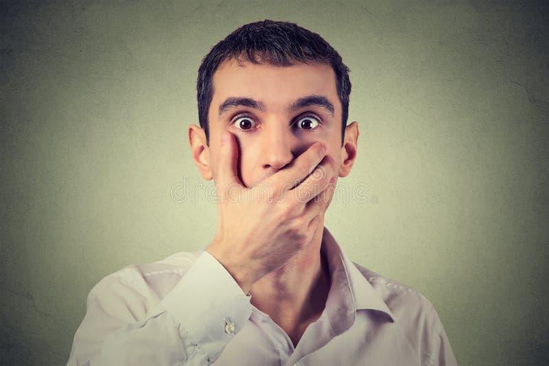 Förskräckt ung man med handen över hans mun som bedövas och som är mållös royaltyfri bild