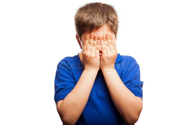 Förskräckt unge som täcker hans framsida arkivbild