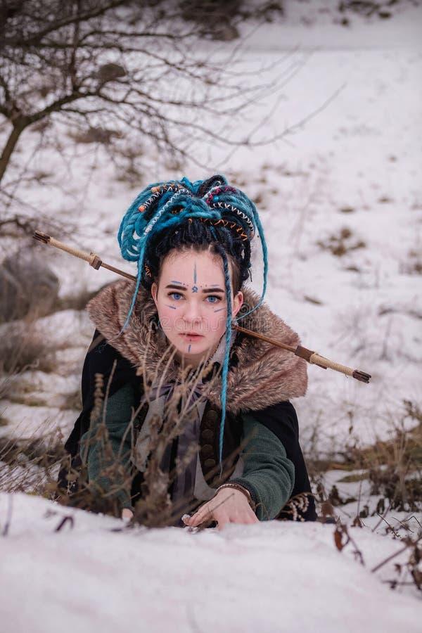 Förskräckt vikingkvinna med ett svärd i ett svart långt ansvar med päls Stående av en drömlik flicka kvinnligt med blåa hårdreadl royaltyfri fotografi