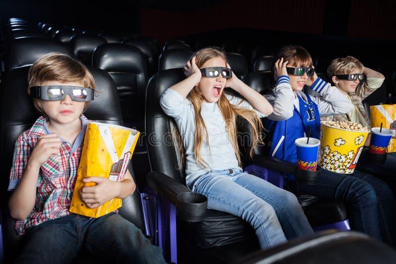 Förskräckta barn som håller ögonen på filmen 3D i bio royaltyfri fotografi