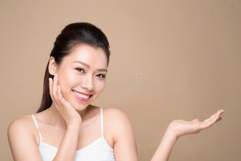Förslag av en produkt Härlig brunnsortkvinna som visar tom kopieringsspac fotografering för bildbyråer