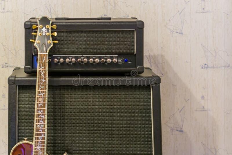 Förstärkare och ask för solid effekt med en gitarrhals, yrkesmässig musikutrustningbakgrund royaltyfri fotografi