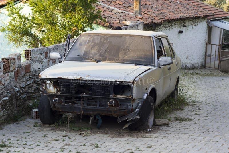 Förstörd bil bredvid den stenlade vägen royaltyfri foto