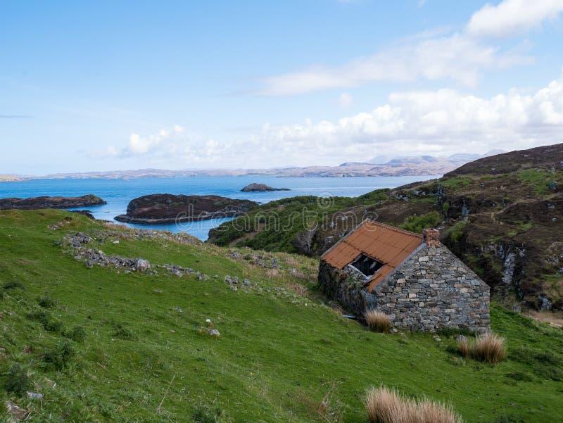 Förstörd ladugård som förbiser havet i nord av Skottland royaltyfria bilder
