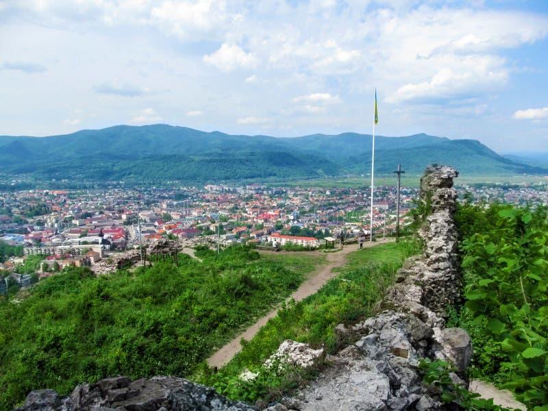 Förstörd vägg av den Khust fästningen och panoraman av Khust på en bakgrund av Carpathians - bästa sikt Det ljuva landskapet av arkivbilder