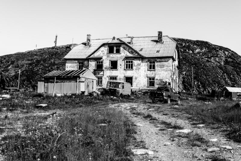 Förstört gammalt övergett stenhus i byn Teriberka en selo i det Kolsky området av Murmansk Oblast, Ryssland royaltyfri fotografi