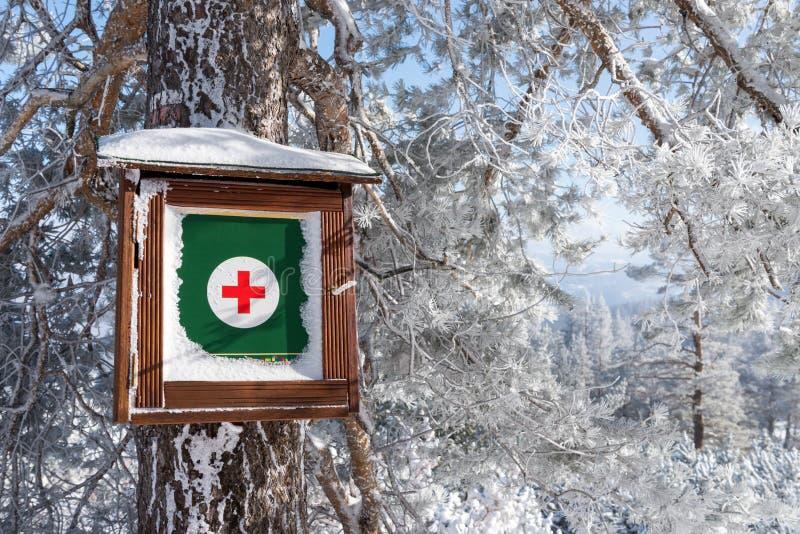 Första hjälpensatsen som hänger på trädstammen i snö, täckte skogen royaltyfria foton