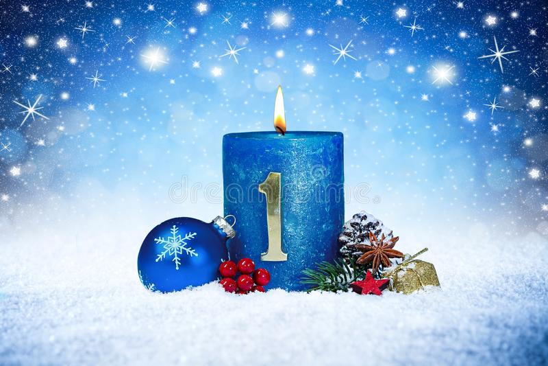 Första söndag av den blåa stearinljuset för advent med röd garnering en för guld- metallnummer på träplankor i snöframdel av silv royaltyfri bild