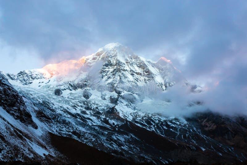 Första solstrålar som tänder maximumet av monteringen Annapurna södra 7219 M på soluppgång, Annapurna basläger, Annapurna naturvå arkivfoto