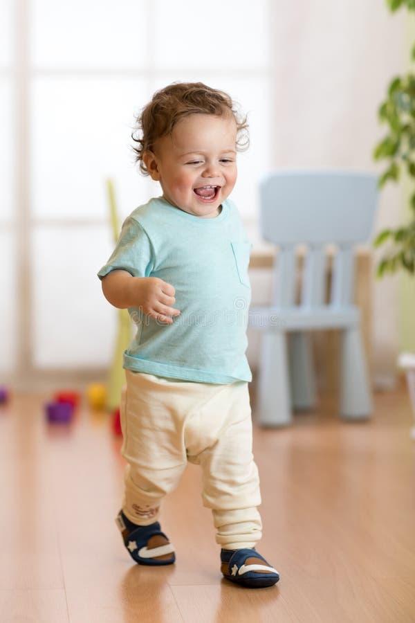 Första steg av behandla som ett barn lilla barnet som lär att gå i vardagsrum Skodon för små barn arkivbild