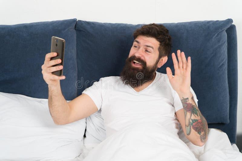 Första ting i morgon Skäggig hipster för man som surfar sociala nätverk för internet Säg hälsningar till vänner Online-kommunikat fotografering för bildbyråer