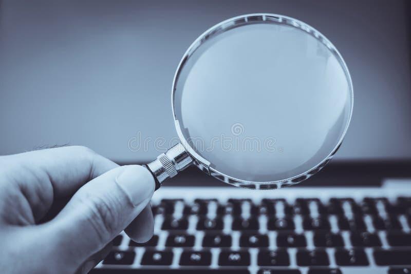 F?rstoringsglas med b?rbar datorbakgrund arkivbild